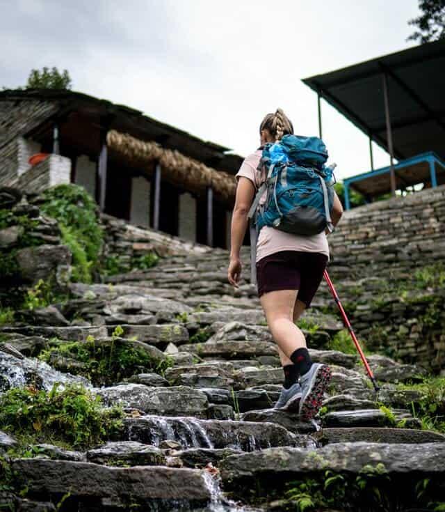 Persona practicando senderismo, subiendo una escalera de piedras